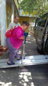 Rámpa segítségével száll be az autóba a két bottal járó lány.